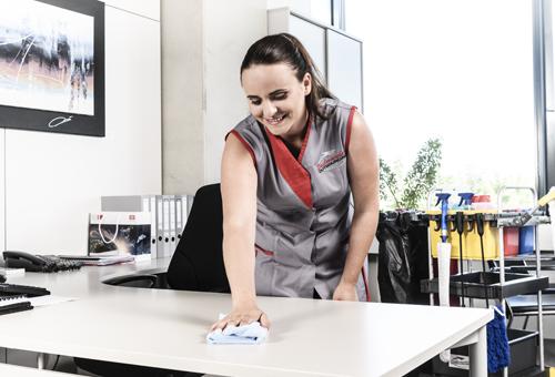 Reingungsfachkraft desinfiziert Büroräumlichkeit